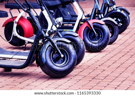 Ranks of minibikes on the street. Personal transport. electric motorcycle. The concept transport with an electric motor of ecology and traffic safety in the city. #1165393330