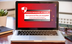 Ransomware text on computer screen, Cyber attack concept. Office business wood desk background.
