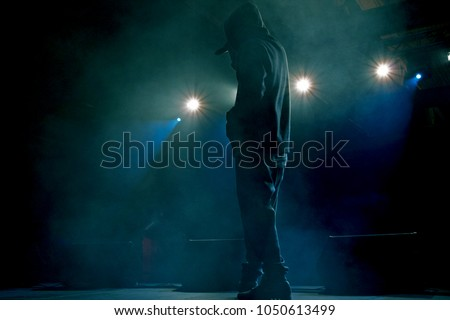 Rap artist on stage in the rays of soffits light. Concert backlight and illumination during music concert. Singer in hoodie with microphone at stage Stock foto ©