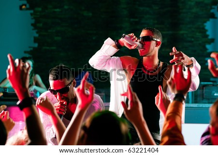 Rap or Hip-Hop Musicians performing on stage in a club in front of a cheering crowd #63221404