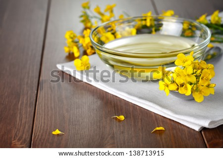 Rapeseed oil with flower of rapeseed. Food composition on wooden table #138713915