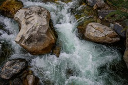 Rapid and powerful water flow between large rocks, close-up. Boulders in cold mountain river. Natural backgrounds.