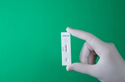 Rapid antigen COVID-19 test. Quick rapid diagnostic test with positive results. Hand holds antigen test on green screen. copy space