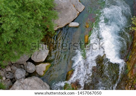 Rapid flow of water flows around the stones and forms white foam in the mountain river. Aerial view, daylight, bright colors. Bielsa, Aragon, Spain   #1457067050