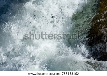Rapid water of waterfall close-up (nature background).