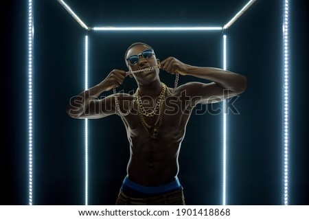 Rapper in gold chains poses in illuminated cube Stock fotó ©