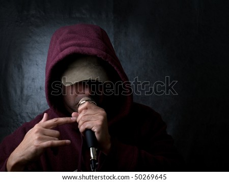 Rapper wearing hood and singing to a microphone