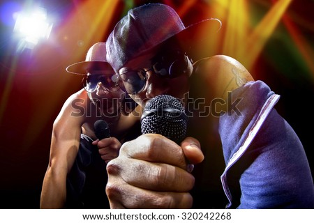 Rappers having a hip hop music concert with microphones.  The arrogant musician is having a concert in a nightclub.