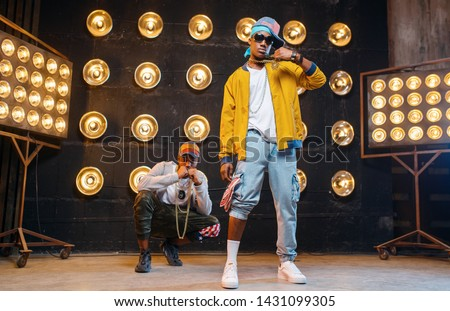 Rappers in caps dance on stage with spotlights Stock fotó ©