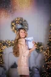 Rapturous slim woman with long curly hair in elegant dress holding christmas present box in festive living room with Christmas decor with garland lights. Christmas Christmas Eve concept. Greeting card