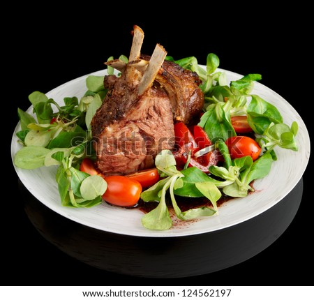 Rare fried rack of lamb isolated on black background with reflection