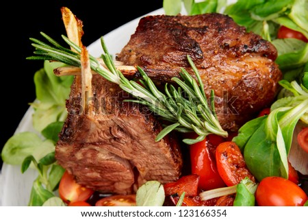Rare fried rack of lamb isolated on black, close-up