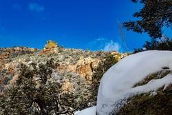 Rare snow on the Finger Rock hiking trail near Mount Kimball in the Catalina Mountains north of Tucson, Arizona. Steep rocky cliffs, snowy pine trees and boulders with blue skies. Winter of 2019.