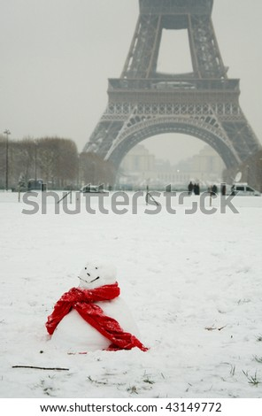 Rare snowy day in Paris. Funny snowman with red scarf and the Eiffel Tower