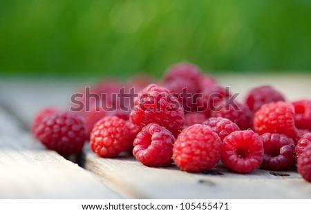 Rasberries fruit on wooden background outdoor - stock photo