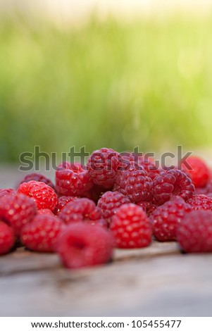 Rasberries fruit on wooden background outdoor