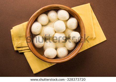 Rasgulla or rosogulla - an Indian sweet made from khoya, soft and spongy, in earthen bowl over yellow napkin and brown background, top view closeup, isolated