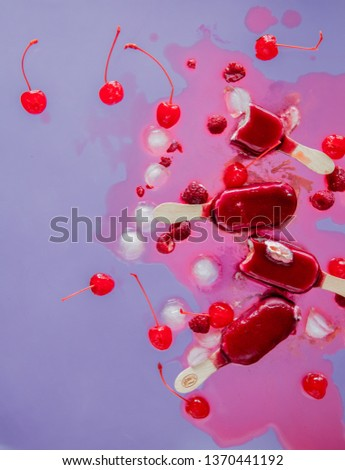 raspberries and cherry ice lollys on purple background. Object without shadows