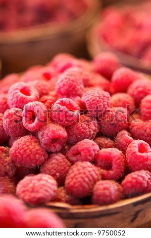 Raspberries for sale in a basket on a market stall