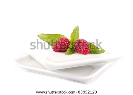 Raspberries in a white plate on a white background