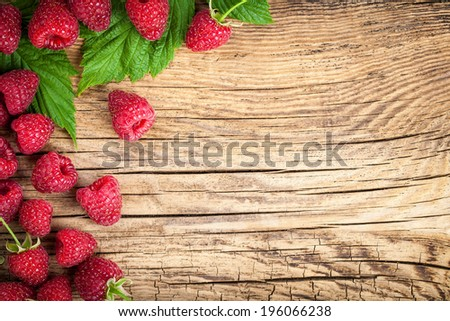Raspberries on wooden table background