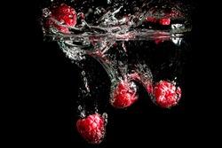 Raspberries splashing into water. Fresh berry fruit on black background.