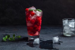 Raspberry alcoholic cocktail with liqueur, vodka, ice and mint on a dark background. Raspberry Mojito. Refreshing cool drink, lemonade or ice tea in a glass. Close up, copy space for text, low key