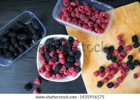 Raspberry and blackberry berries on a wooden background. Red ripe raspberries and ripe blackberries. #1435956575