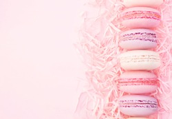 Raspberry and strawberry pink macarons on pastel valentine decor and rose flowers soft background, selective focus, toned