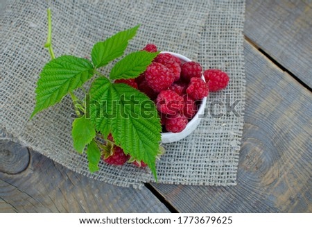 Raspberry berries in a ceramic dish on a burlap and wooden surface with a green leaf