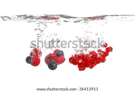 raspberry, blackberry and gooseberry splash in water isolated on white
