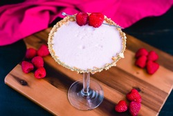 Raspberry Cheesecake Martini with a Berry Garnish: Raspberry cheesecake martini in a cocktail glass rimmed with graham cracker crumbs