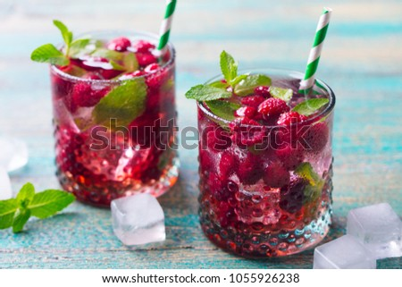Raspberry cocktail, fizz, lemonade, ice tea with fresh mint on blue wooden background. Close up.