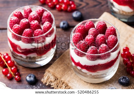 Raspberry dessert, cheesecake, trifle, mouse in a glass on a wooden background. #520486255