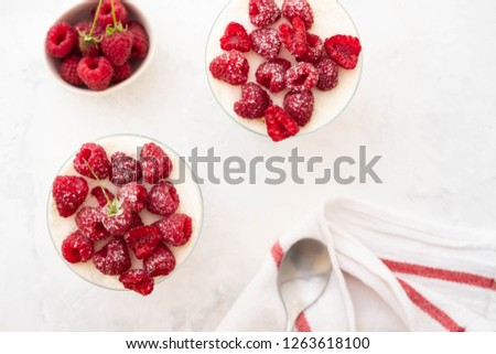 Raspberry dessert, raspberry tiramisu, cheesecake, trifle, mousse in a glass on a wooden background.Top view