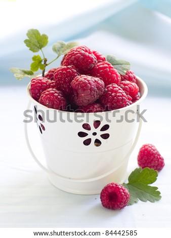 Raspberry in white bucket. Selective focus - stock photo