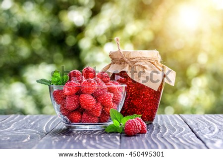 Raspberry jam  and fresh raspberry on a rustic wooden table outdoors