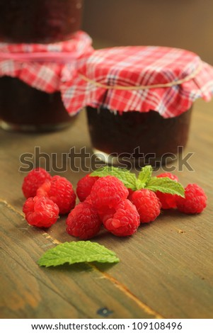 Raspberry jam, fresh fruits and mint on a wooden table