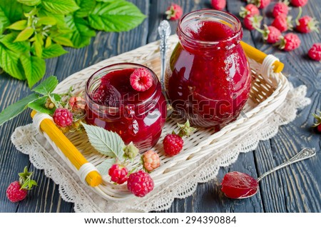 Raspberry jam ( marmalade ) and fresh raspberry on a rustic wooden table.Selective focus