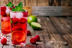 Raspberry Mojito Lemonade with lime and fresh mint in glass on wooden background. Summer refreshing cocktail.