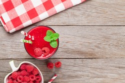 Raspberry smoothie and berries in bowl on wooden table. Top view with copy space