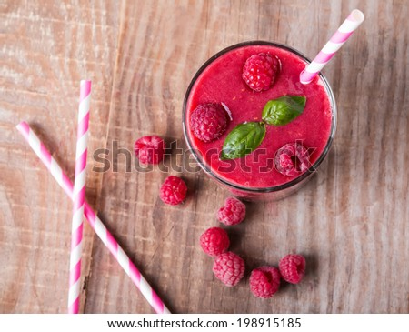 Raspberry smoothie in a glass on wooden table, up view