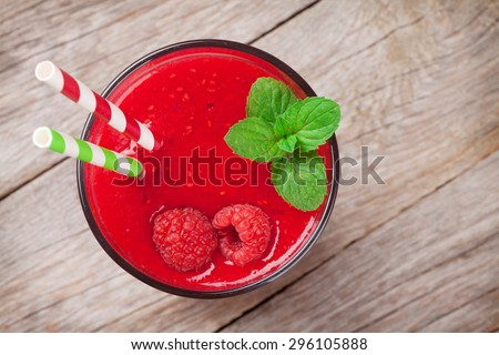 Raspberry smoothie with berries on wooden table Top view
