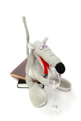 Rat and a glass. Symbol of 2020. Cute gray rat sits on a stack of books on a white background close-up. In front of her is an elegant glass goblet on a long leg.