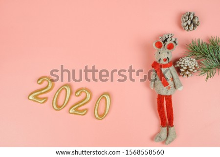 Rat toy as a symbol of 2020 on a pink pastel background. Figures 2020 and Christmas tree branch with cones. Copyspace, flatlay.