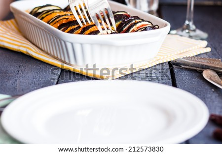 Ratatouille in white casserole and blank round plate,serving food