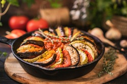 Ratatouille made of zucchini, eggplants, peppers, onions, garlic and tomatoes slices with aromatic herbs. Rustic wooden table. Traditional French food, vegetable, vegan healthy dish. Copy space