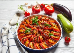ratatouille, vegetable stew of sliced eggplant, zucchini, onion and potato with tomato sauce, ingredients at the background, french cuisine, horizontal view from above