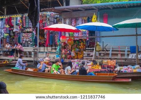 Ratchaburi, Thailand - August 14th, 2017. Tourists are enjoying with shopping on the boat at Damnoen Saduak floating market. #1211837746