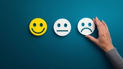 Rating concept. Woman choosing sad or bad smiley face emotion on green background, panorama, copy space